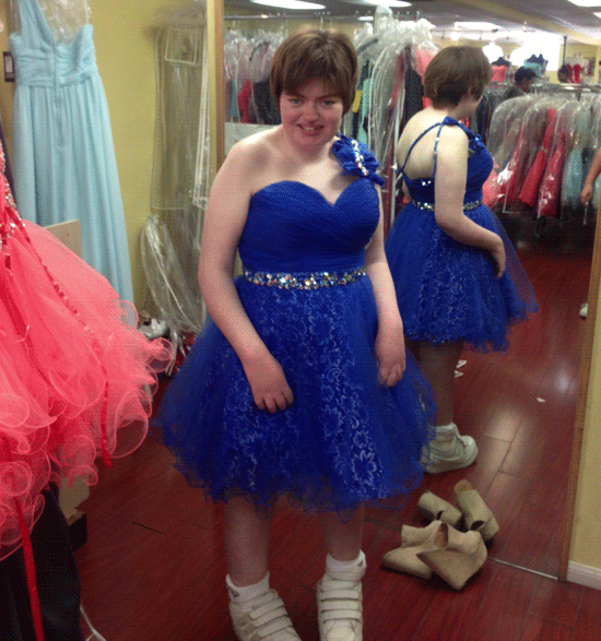 Siobhan in a cobalt blue sparkly dress in front of a mirror showing straps at one shoulder