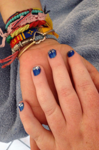Siobhan's hand in Juliana's hand showing cobalt blue nail polish with silver glitter tips.