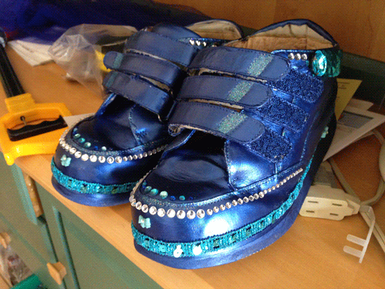 Siobhan's big orthopedic shoes painted iridescent blue with applied crystals and bangles and a miniature crystal bow on the very front