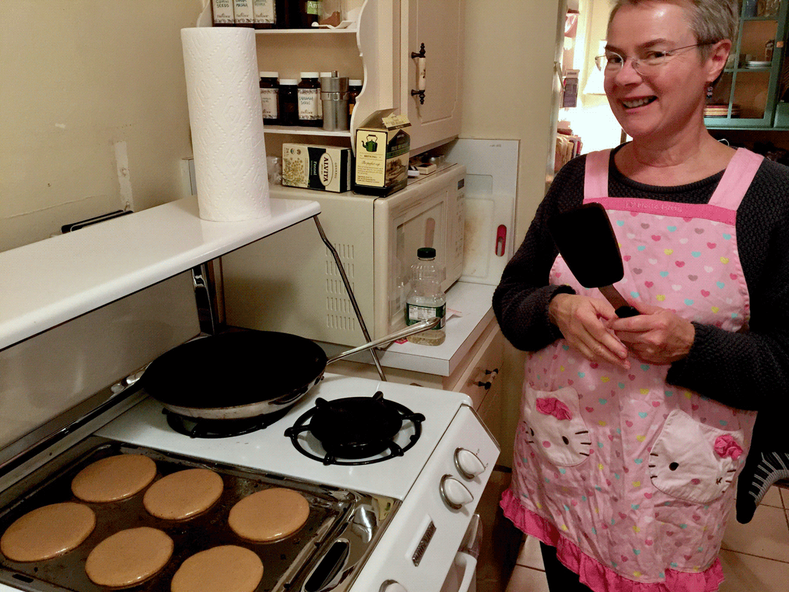 Linda hoding spatula in Hello Kitty apron with six pancakes cooking on the griddle