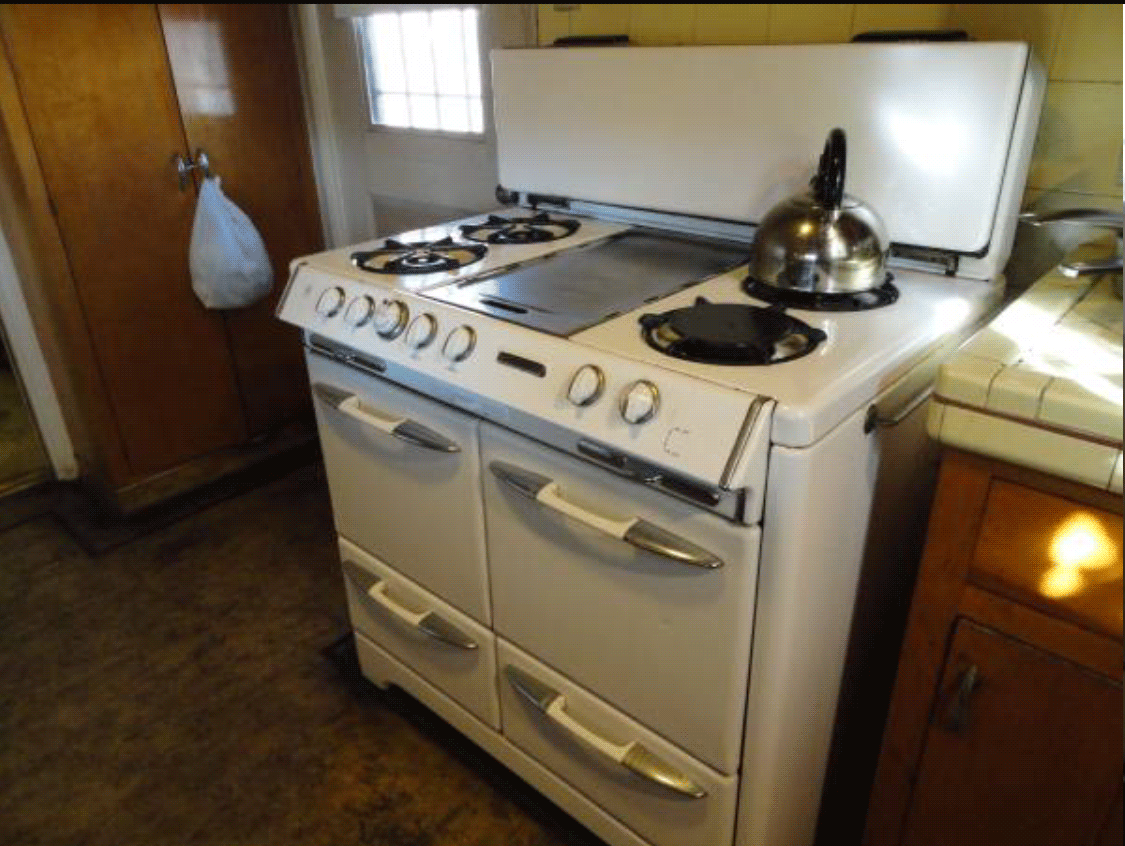 Stove with double oven doors and pancake griddle top center in old fashioned kitchen