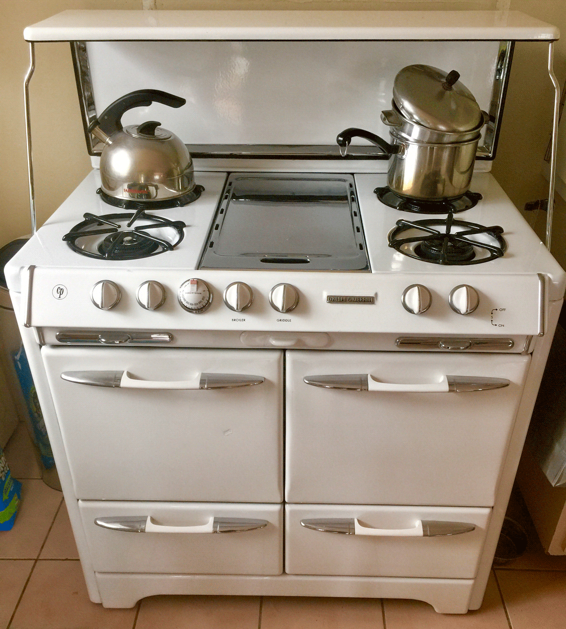 Stove with lid folded up fourd doors on front four burners and chrome pancake griddle in middle of cooktop