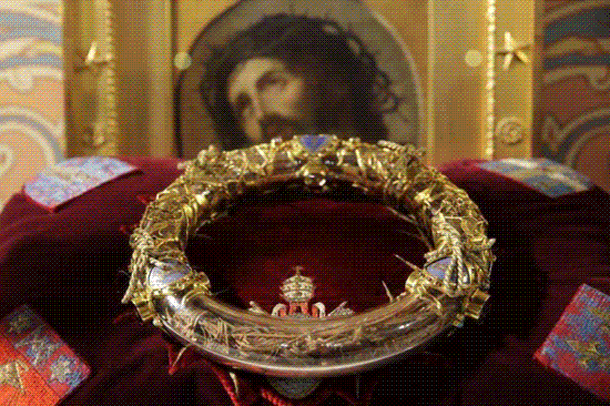 crown of thorns in ornate gold and crystal reliquary on velvet cushion in front of portrait of jesus wearing crown